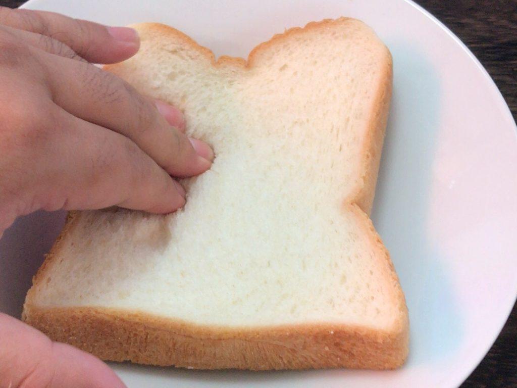 食パンを手で押してくぼみを作っている