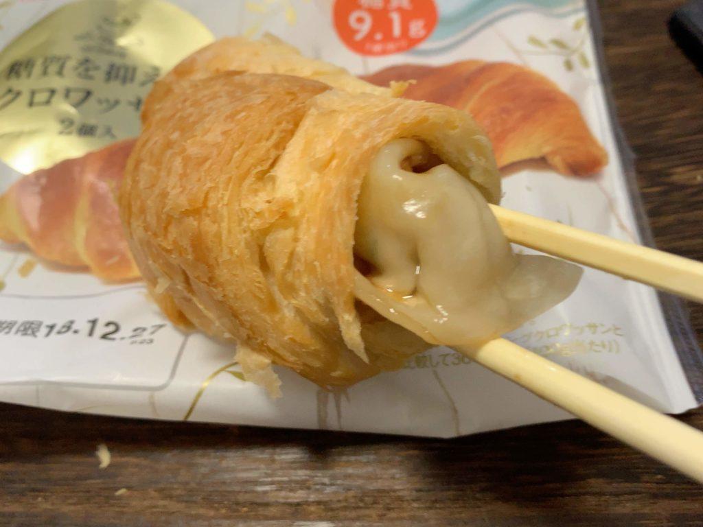 箸で餃子をクロワッサンに入れている