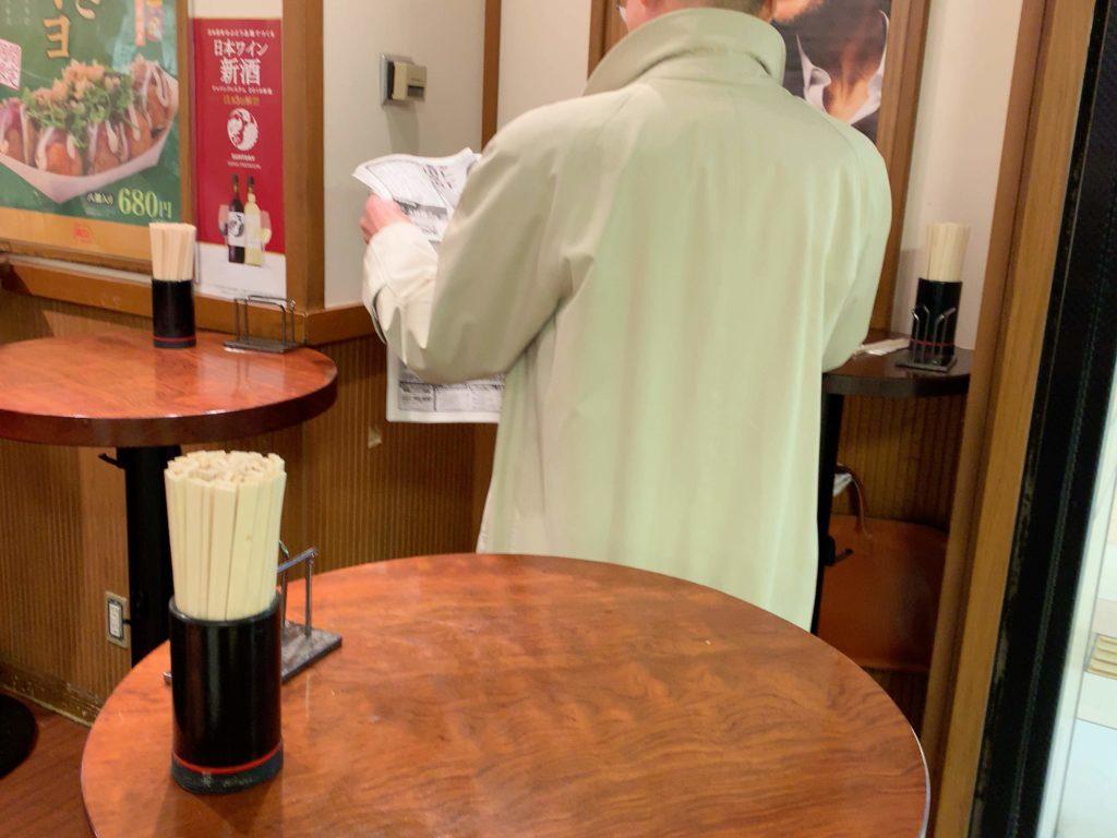 新聞を読んでいる男性の後ろ姿