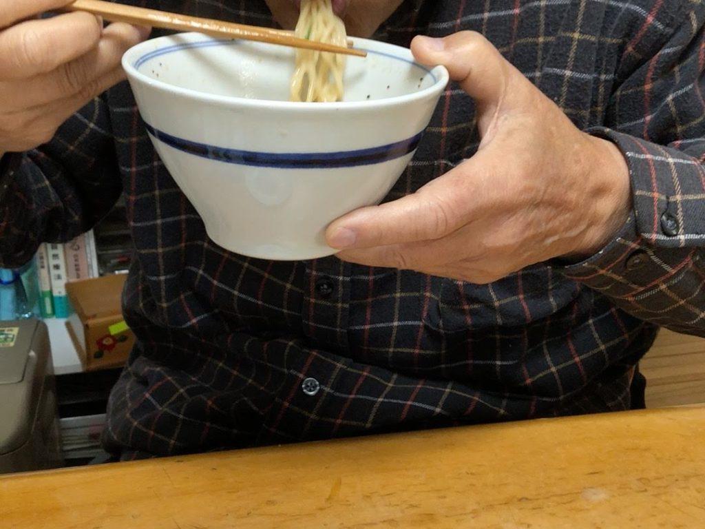 男性がラーメンを食べている