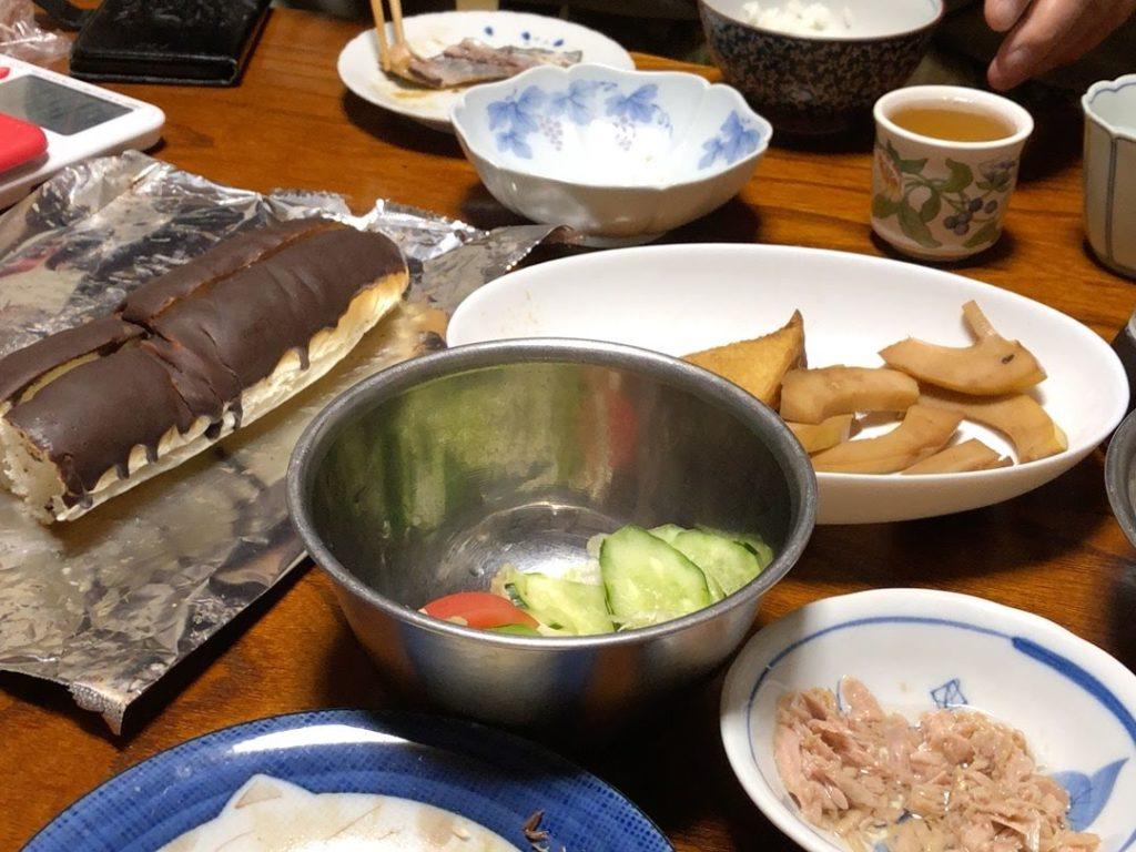 和食が並んだ食卓の中にチョコのかかったパンが置いてある