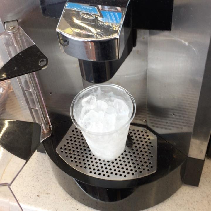 コーヒーメーカーに氷の入ったカップをセットしている